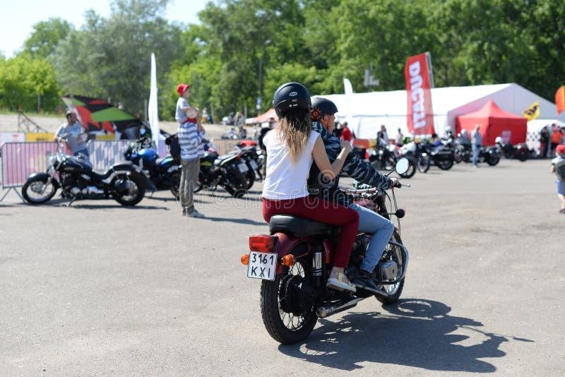 Type avec une fille montant une moto photographie stock