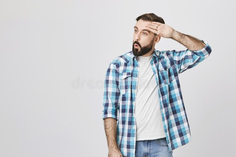 Type barbu adulte essuyant son front avec la main faisant ouf le geste, exprimant le soulagement tout en se tenant contre le mur  image stock