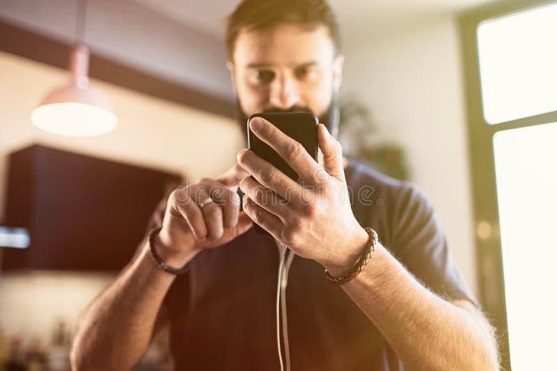 Type barbu attirant portant la musique de ?coute de T-shirt gris occasionnel dans des ?couteurs, v?rifiant les r?seaux sociaux su photos libres de droits