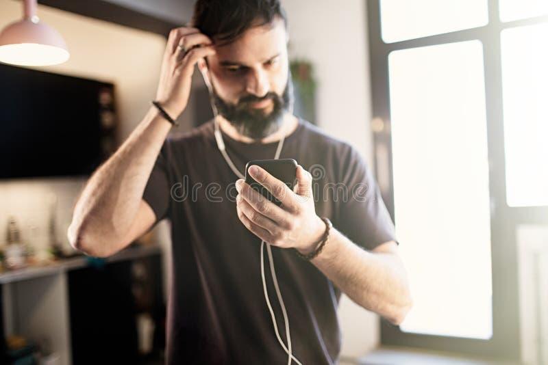 Type barbu beau portant la musique de ?coute de T-shirt gris occasionnel dans des ?couteurs, v?rifiant les r?seaux sociaux sur le photographie stock