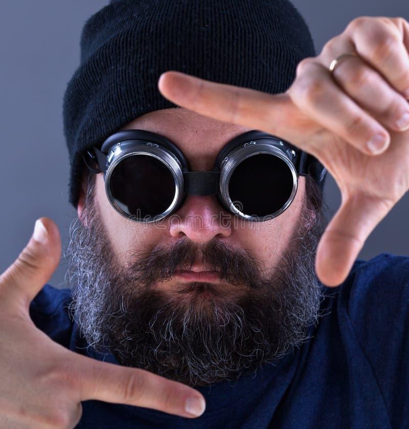 Type barbu encadrant une photo devant son visage photo libre de droits