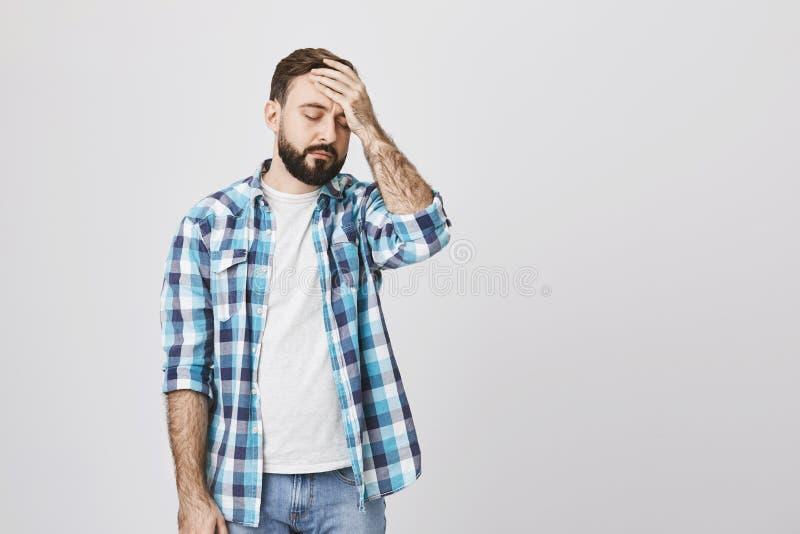 Type barbu malheureux fatigué en test la chemise, tenant la main sur le front, se tenant sur le fond gris homme d'affaires mascul photos stock