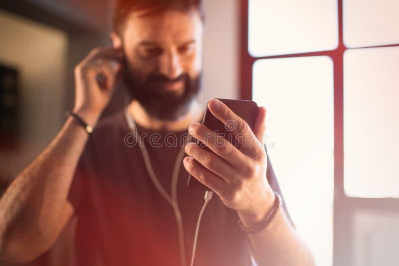 Type barbu sûr portant la musique de écoute de T-shirt gris occasionnel dans des écouteurs, vérifiant les réseaux sociaux su photos stock