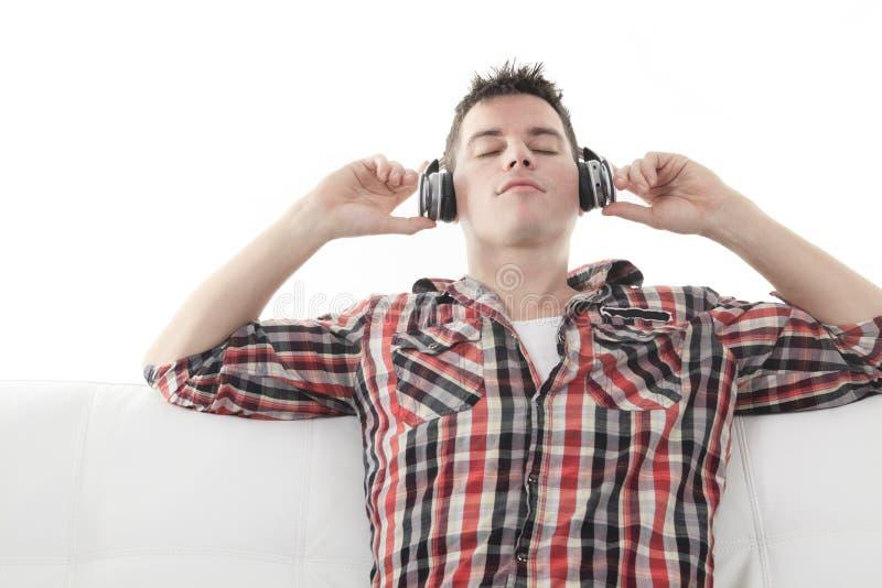 Type beau appréciant la musique sur des écouteurs image stock