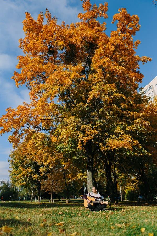 Type beau avec la guitare en parc d'automne photographie stock libre de droits