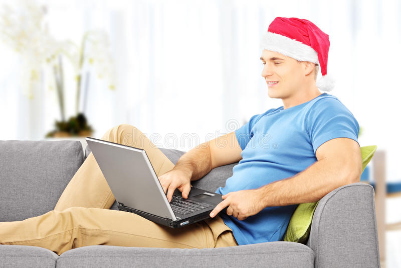 Type beau avec le chapeau de Santa sur un sofa travaillant sur un ordinateur portable au hom photographie stock