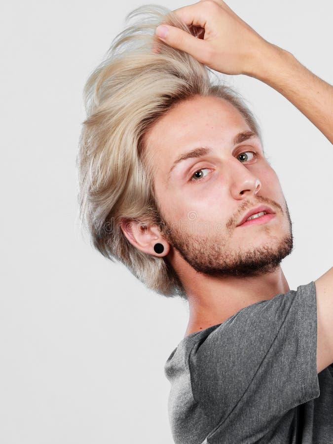 Type beau blond touchant ses cheveux photo stock