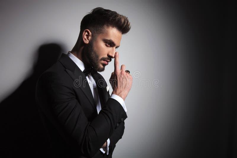 Type beau dans le smoking noir dirigeant son nez photo libre de droits