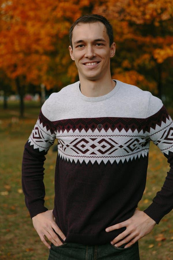 Type beau dans un chandail en parc d'automne images libres de droits