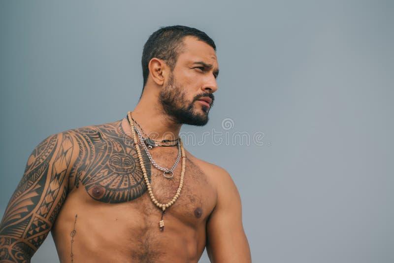 Type beau Homme musculaire avec le corps parfait abs Buts de corps Fond gris photos stock