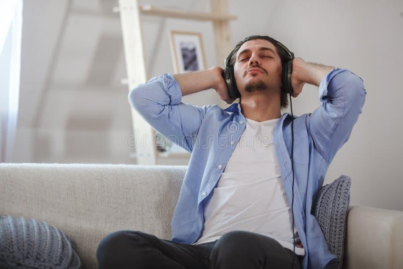 Type beau s'asseyant sur le sofa avec des écouteurs image stock