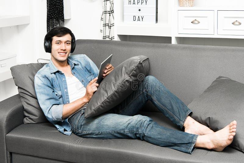 Type beau s'asseyant sur le sofa avec des écouteurs photos libres de droits