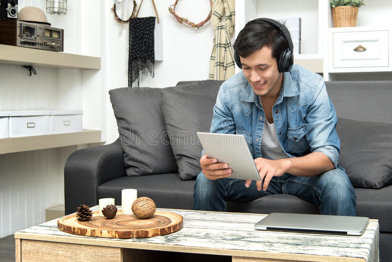 Type beau s'asseyant sur le sofa avec des écouteurs images stock