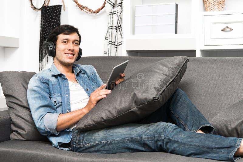 Type beau s'asseyant sur le sofa avec des écouteurs photos stock