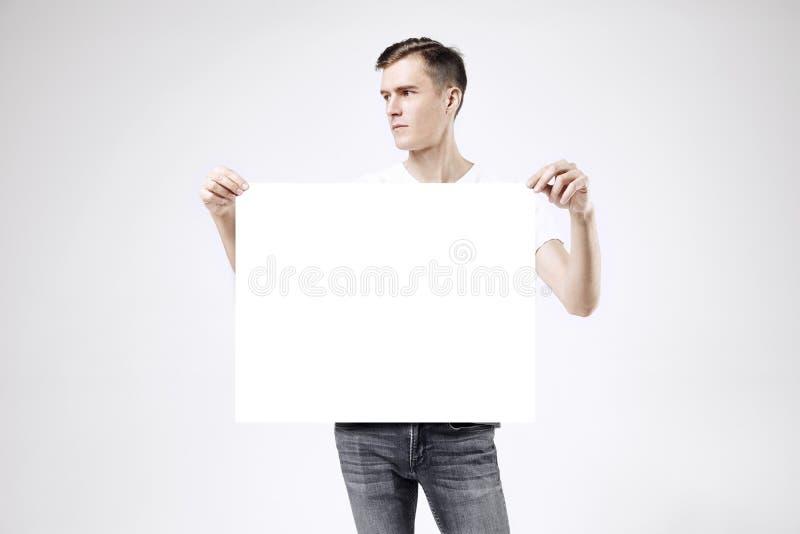 Type beau se tenant avec la grande affiche ou feuille vide dans des mains, d'isolement sur le fond blanc, les jeans de port et le photos libres de droits