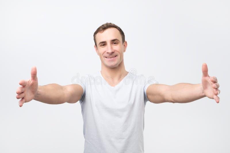 Type beau tirant des mains vers la caméra et le sourire amical à la caméra voulant l'étreinte photos stock