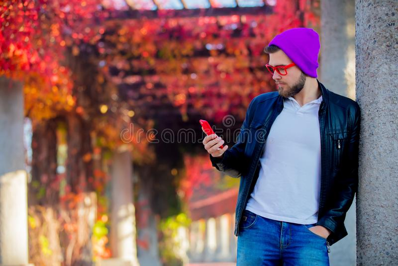 Type blanc à l'aide d'un téléphone portable dans un parc photo stock
