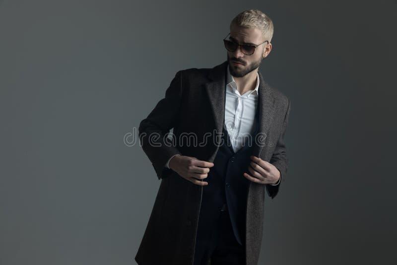 Type blond ajustant son longcoat tout en marchant images libres de droits