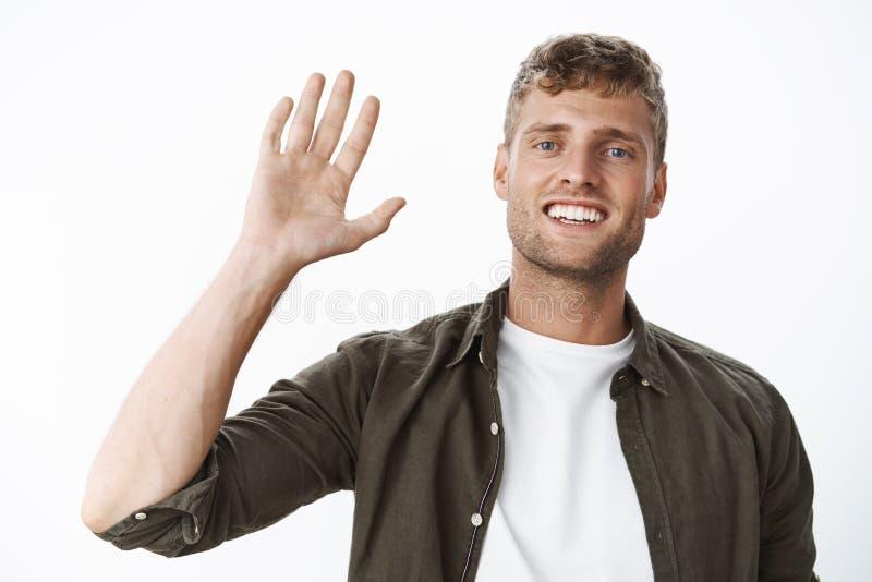 Type blond amical disant l'ondulation de bonjour amicale à la salutation de caméra, souriant largement, étant dans la bonne humeu photo stock