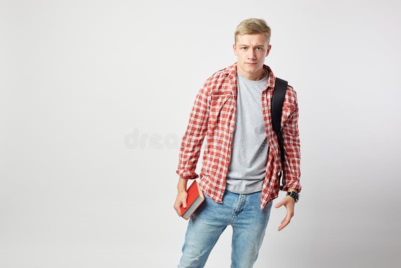 Type blond sérieux avec le sac à dos noir sur son épaule habillée dans un T-shirt blanc, une chemise à carreaux rouge et des pris photographie stock libre de droits