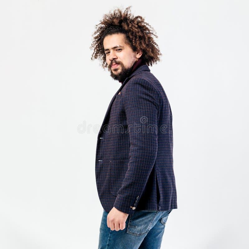 Type bouclé élégant avec une barbe habillée dans le col roulé de Bourgogne, la veste à carreaux grise et les poses de jeans dans  photographie stock