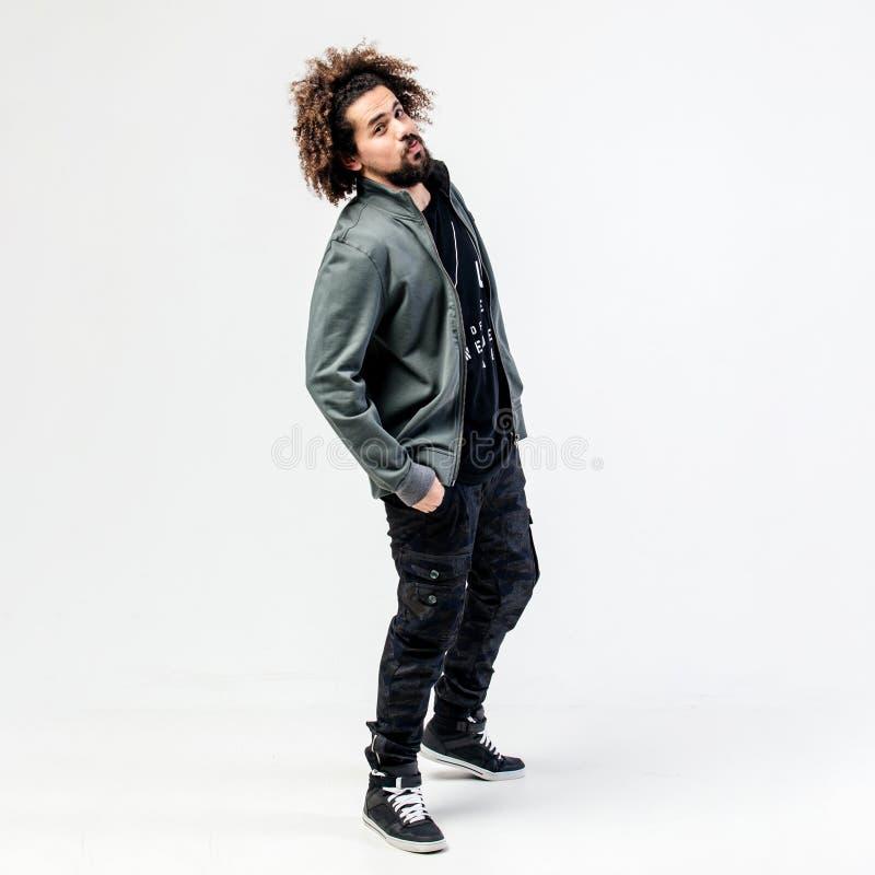 Type bouclé élégant avec une barbe habillée dans un T-shirt noir, une veste grise, un pantalon kaki et des poses d'espadrilles da image libre de droits