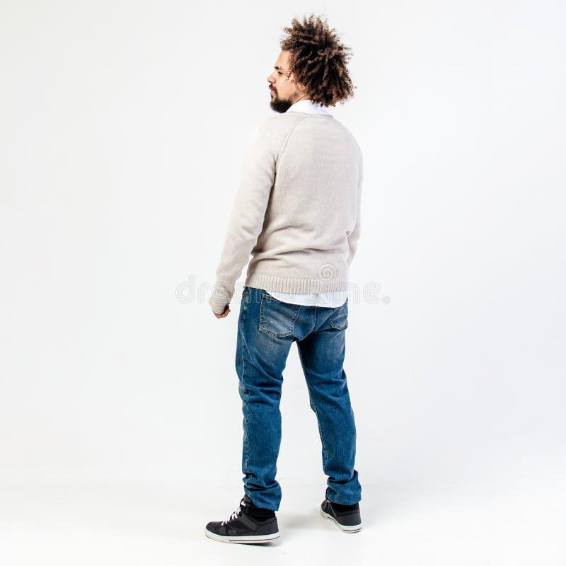 Type bouclé châtain élégant avec une barbe habillée dans le pullover beige au-dessus d'une chemise blanche et les poses de jeans  image stock