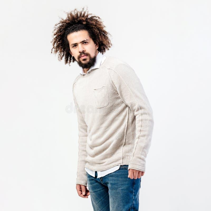 Type bouclé châtain élégant avec une barbe habillée dans le pullover beige au-dessus d'une chemise blanche et les poses de jeans  photographie stock libre de droits