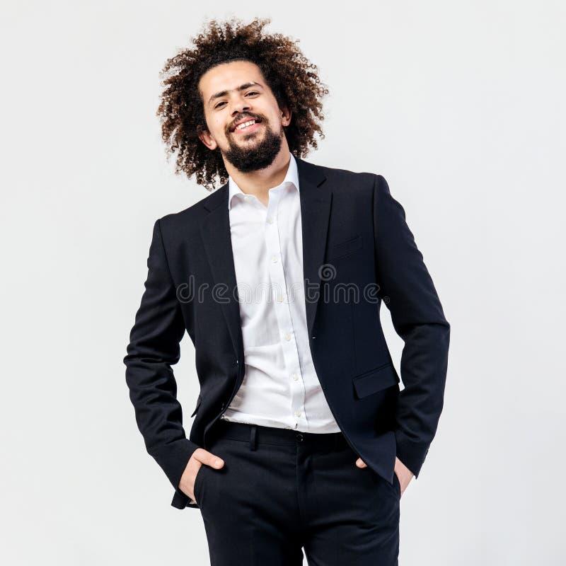 Type bouclé châtain de sourire habillé dans un costume noir classique et des poses blanches de chemise dans le studio sur le blan photo libre de droits