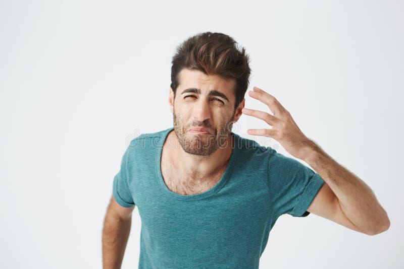 Type caucasien barbu attirant frustrant dans le T-shirt bleu à la mode, avec l'expression folle grincheuse gesticulant avec la ma photo libre de droits