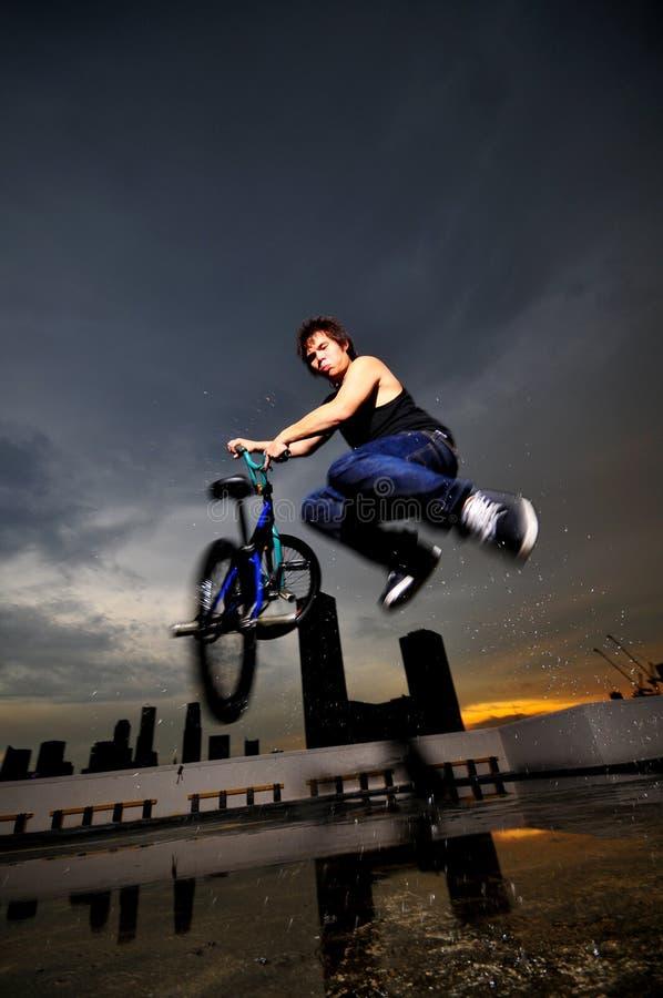 Type chinois asiatique de bicyclette faisant un cascade sur le dessus de toit photographie stock libre de droits