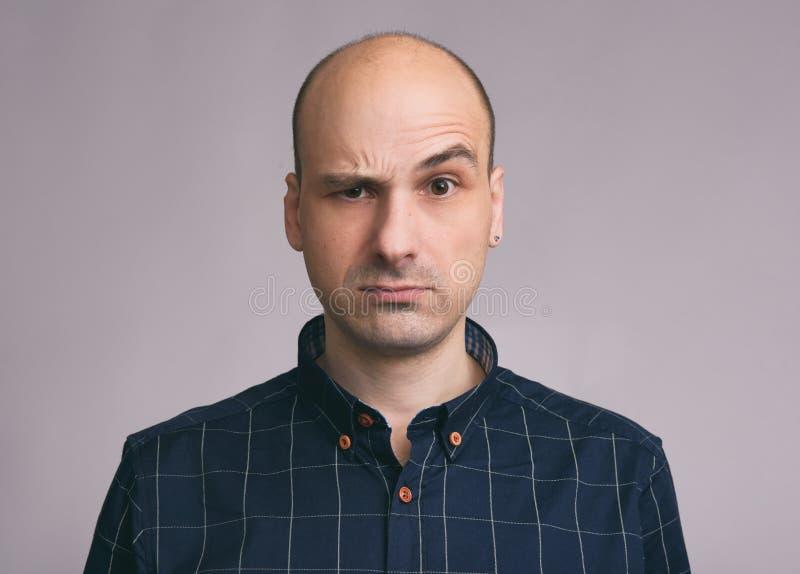 Type confus Jeune homme chauve perplexe photo stock