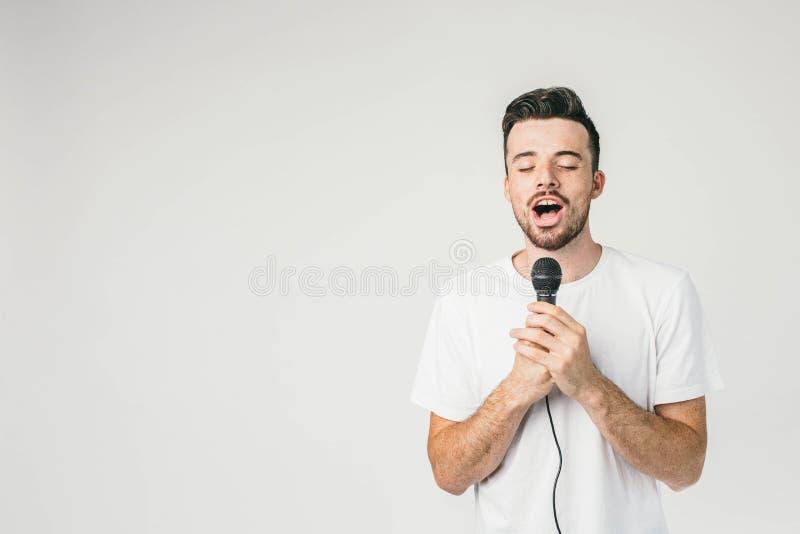 Type courageux se tenant au mur blanc et tenant un microphone avec ses les deux mains Il chante la chanson sensuelle et triste av photos libres de droits