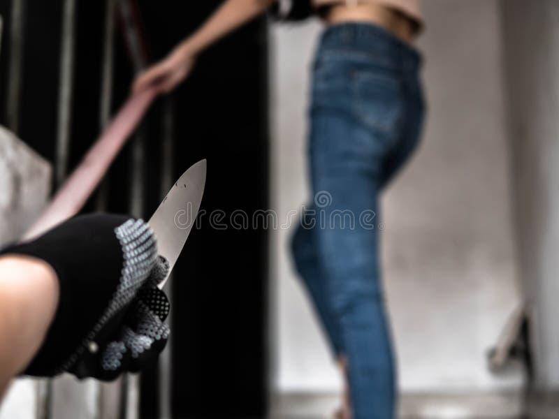 Type criminel inconnu avec le couteau chassant la jeune fille Vol ou viol dans le concept de secteur de bandit, une personne ou l photographie stock libre de droits