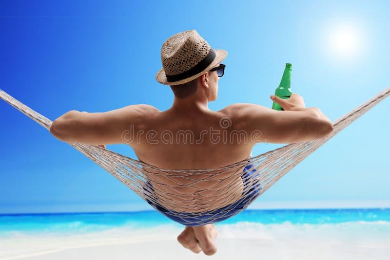 Type décontracté se situant dans un hamac et une bière potable photos stock
