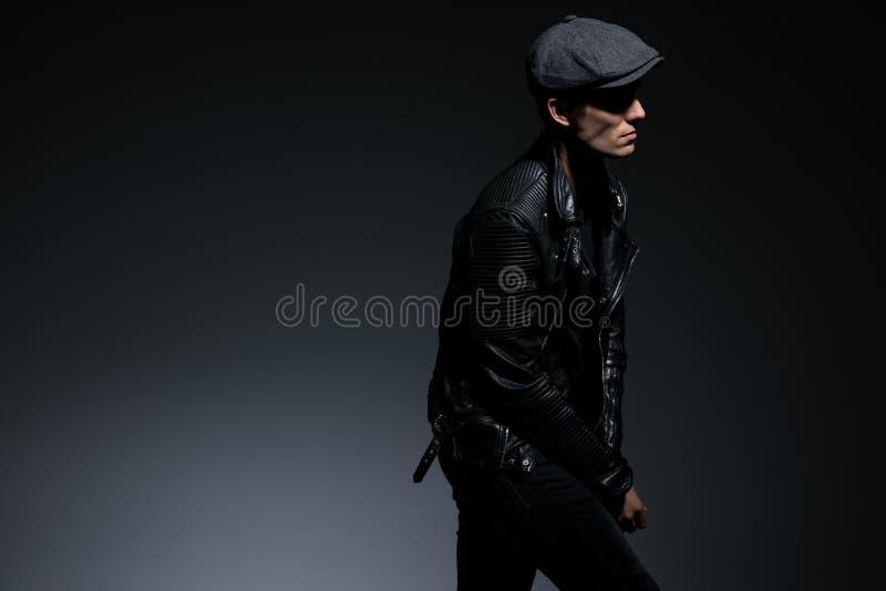 Type dans la main de progression et de penchement de veste en cuir sur le genou images libres de droits