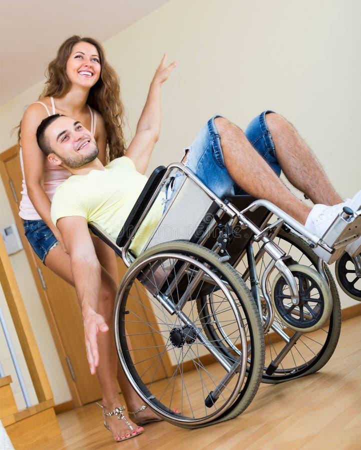 Type dans le fauteuil roulant jouant avec l'ami photo libre de droits