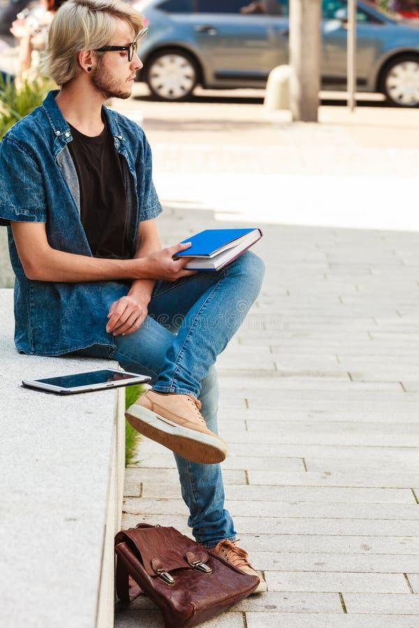 Type de hippie tenant le carnet se reposant sur le rebord photographie stock
