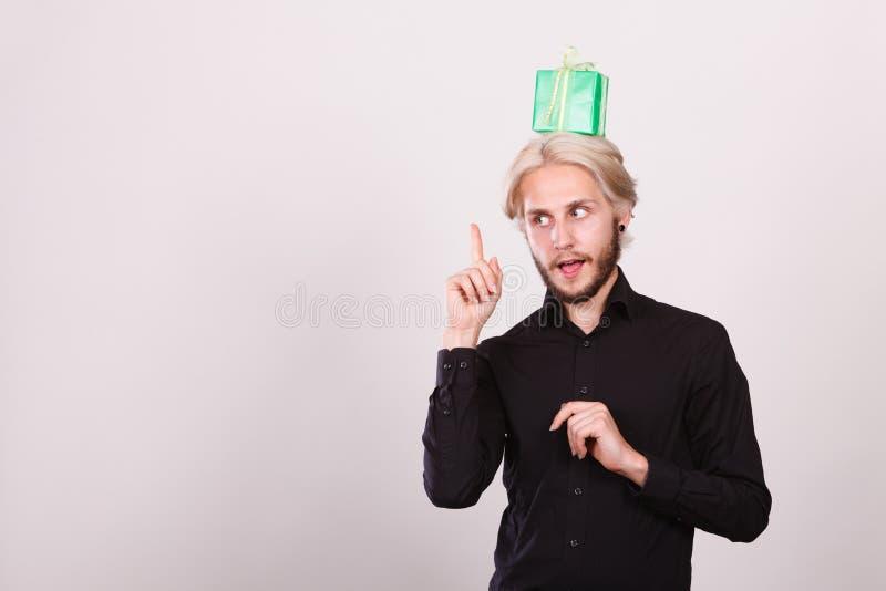 Type de pensée avec le boîte-cadeau vert sur sa tête photos libres de droits