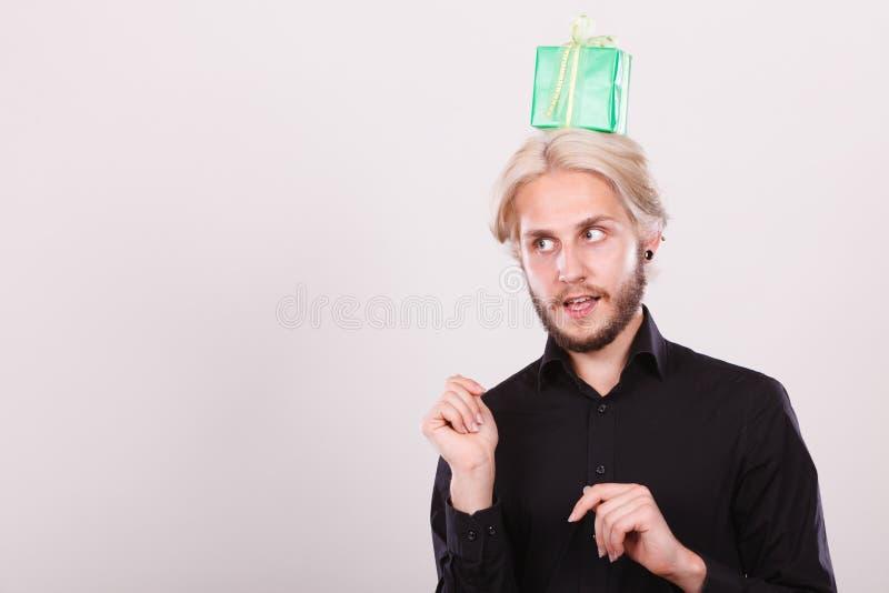 Type de pensée avec le boîte-cadeau vert sur sa tête photo stock