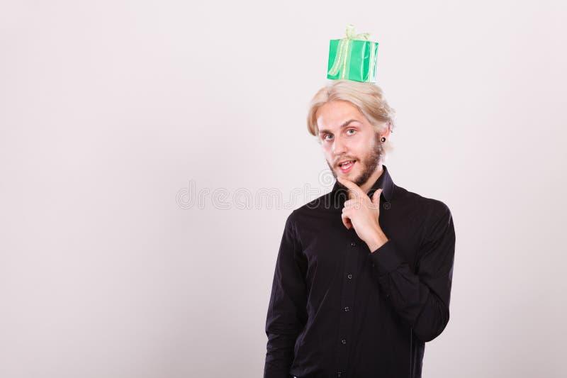 Type de pensée avec le boîte-cadeau vert sur sa tête image stock