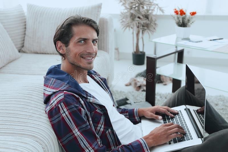 Type de sourire avec un ordinateur portable se reposant sur le plancher près du sofa photos libres de droits