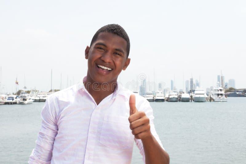 Type des Caraïbes heureux montrant le pouce vers le haut de l'extérieur photos stock