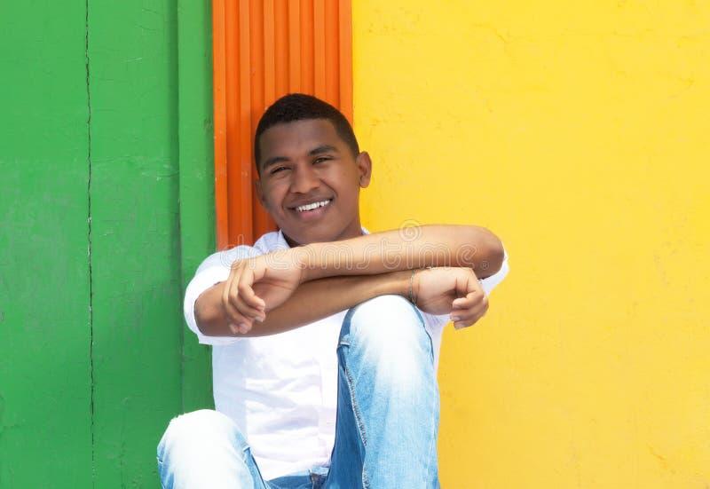 Type des Caraïbes riant s'asseyant devant un mur coloré photos stock