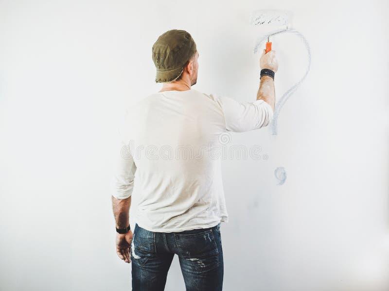 Type effaçant un point d'interrogation sur un mur blanc photo libre de droits