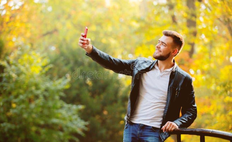 Type employant un appareil-photo de téléphone portable pour un selfie image libre de droits