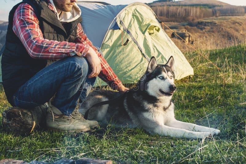 Type en gros plan barbu dans la chemise à carreaux de jeans et une veste sans manche avec une cosse de chien des vacances se repo photographie stock