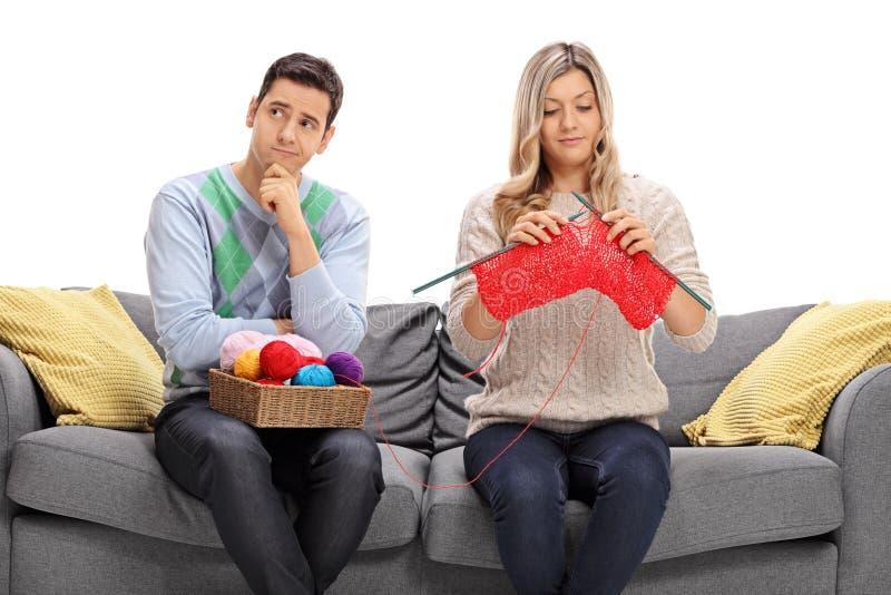 Type ennuyé s'asseyant sur un divan à côté d'un tricotage de femme image stock