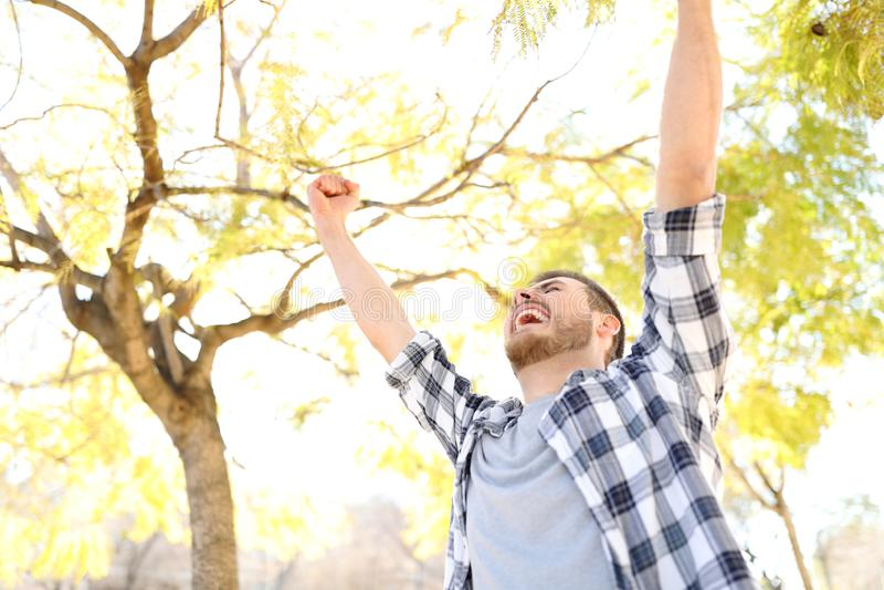 Type enthousiaste célébrant le succès soulevant des bras en parc photo stock