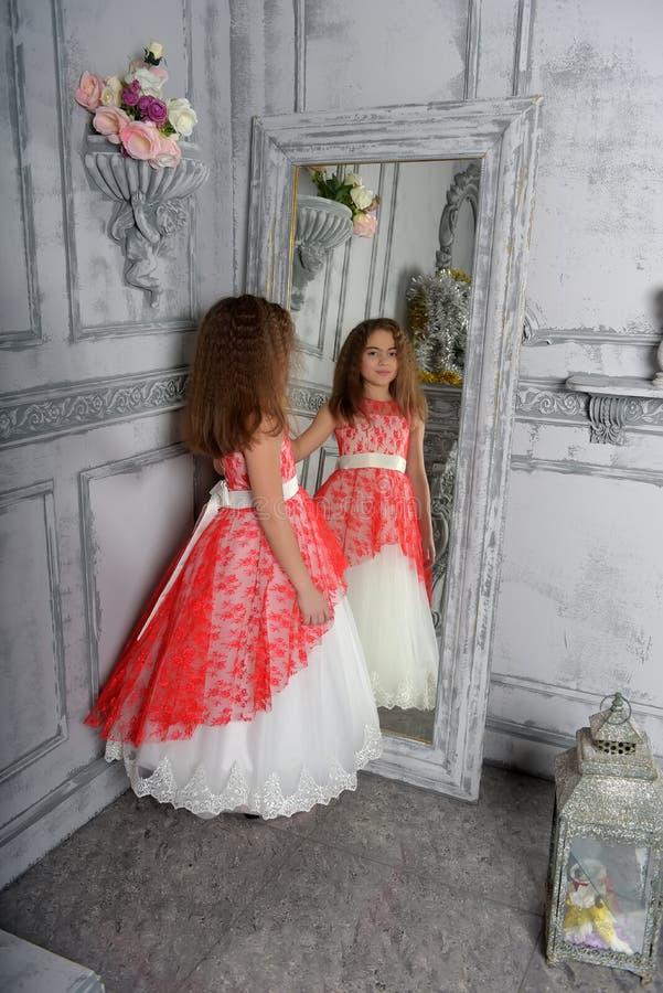 Type est la fille la brune dans le blanc avec une robe ?l?gante rouge photographie stock